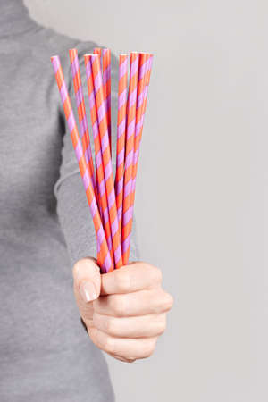 Hand with coctail straw on grey.