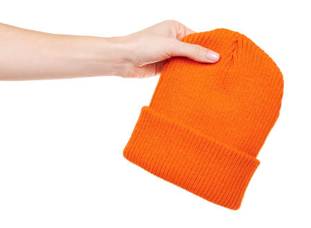 Hand with orange winter hat isolated on white.