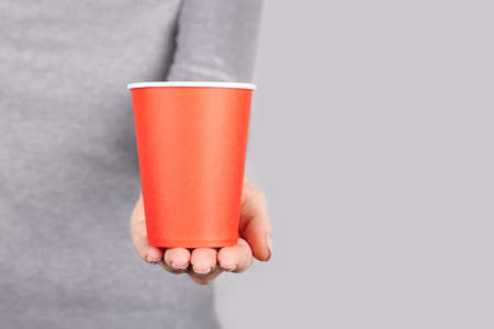 Hand with red disposable cup on grey. Stock fotó
