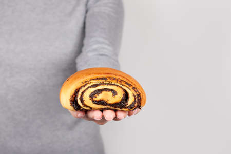 Hand with roll bun with poppy seed on grey. Stock fotó