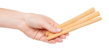 Hand with cookie stick isolated on white.