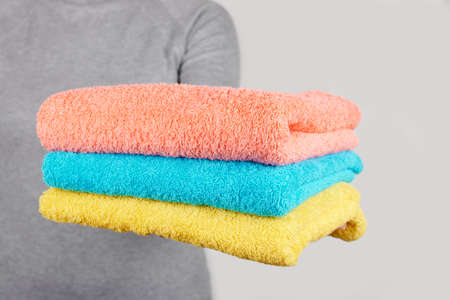 Hand with colored cotton towels on grey