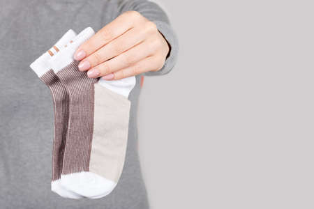Hand with brown cotton socks on grey