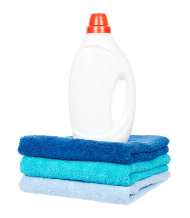 Detergent in bottle with cotton towels isolated on white