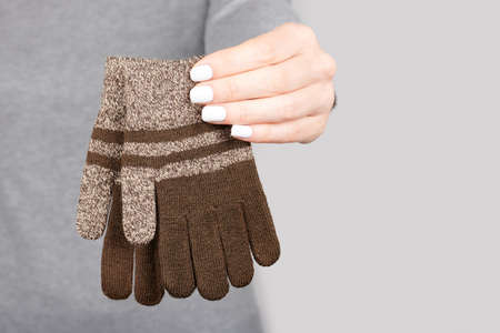 Hand with brown cotton gloves on grey 版權商用圖片