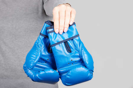 Hand with blue boxing gloves on grey