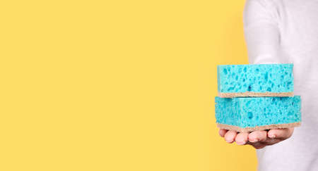 Hand with turquoise cleaning sponge.