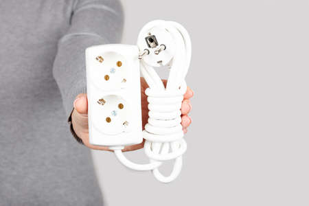 Hand with electric socket extension on grey