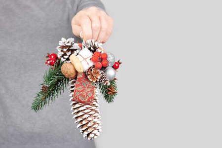 Hand with christmas decoration on grey 版權商用圖片