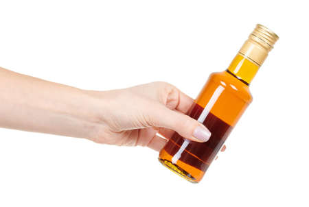 Hand with topping, syrup in glass bottle isolated on white