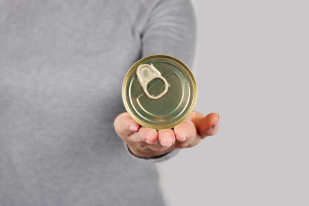 Hand with metal can, preserve tin on grey