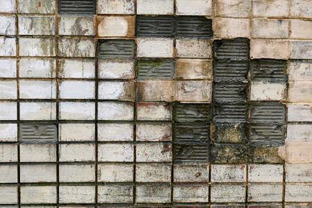 Old cracked ceramic tiles, broken wall.