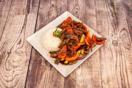 Fantastic traditional Peruvian lomo saltado recipe with portion of white rice, pieces of tenderloin, tomatoes and peppers sauteed with soy sauce French fries on a square white plate Stock Photo