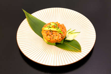 Delicious salmon tartare with pieces of ripe avocado as a base, cucumber slices, trout roe, poppy and sesame seeds and banana leaf underneath