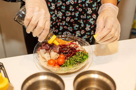 Cook Tuna Poke Bowl Dressing and Smoked Poppet with Cherry Tomatoes, Beets, and Wakame Seaweed Salad in clear plastic home delivery container. Zdjęcie Seryjne