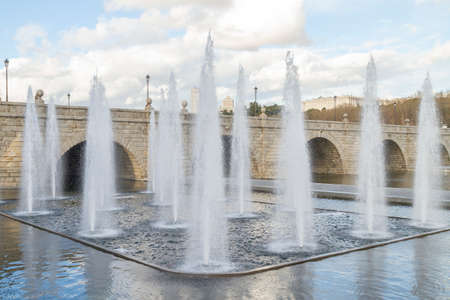 Decorative jets of water rising vertically in the park of Madrid Rio one day with clouds and with the stone bridge of Segovia in the background