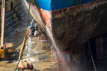 Workmen cleaning corrosion from the hull of a merchant ship with pressure sandblasting in a dry dock of a modern shipyard Stock Photo