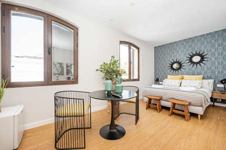 Small studio with king size bed and black multipurpose table in a vacation rental apartment building