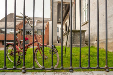 brown makeup color bike hooked to a metal fence Banque d'images