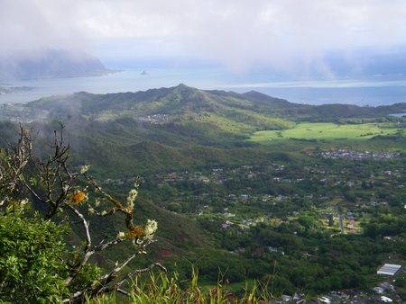 haiku: View of Kanehoe Bay from the Haiku Stairs.  Beautiful mountains, green valley and ocean in the distance.  Whisps of clouds Stock Photo