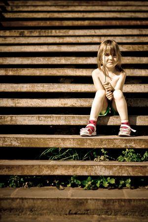 wees: Één kind zit op de trap. Crossprocess.