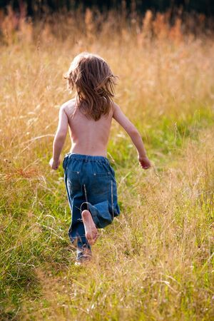 A child running along a path in the field. Sunny photo. photo