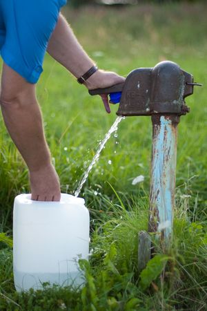 collects: A man collects the water from the old fashioned water pump