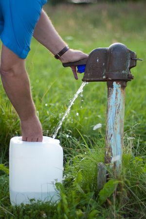 collect: Un hombre recoge el agua de la bomba de agua de moda antigua