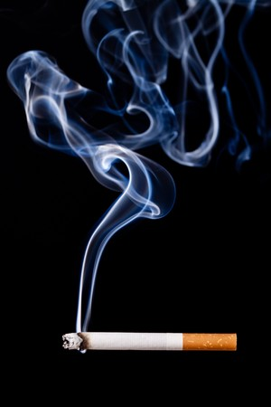 Smoking cigarette. Isolated on black. Closeup. photo