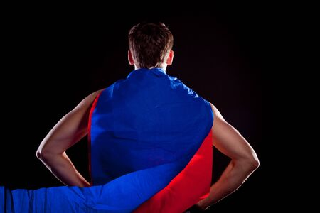 Superhero. On black background. Red-blue cloak.