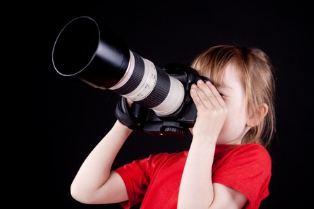 The child - photographer. On black background. photo