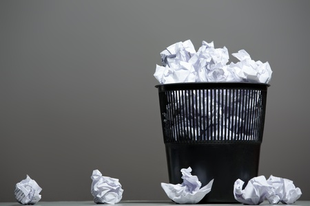 Recycle bin filled with crumpled papers photo