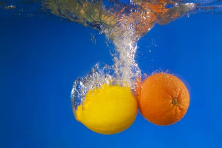 Lemon and orange under water photo
