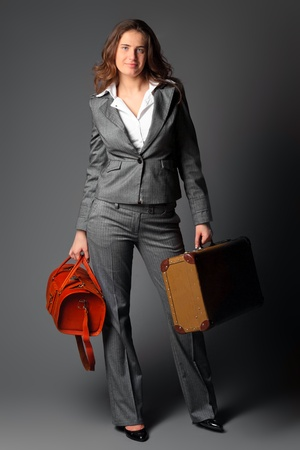 A businesswoman with a bag and a suitcase. Stock Photo - 11230772