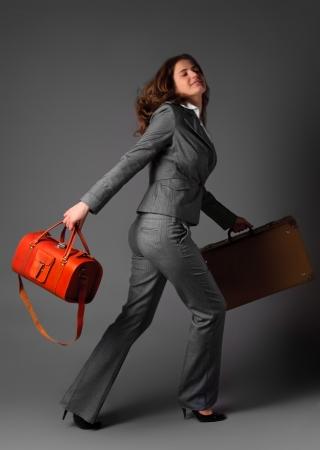 bussines: Een zakenvrouw met een tas en een koffer. Stockfoto