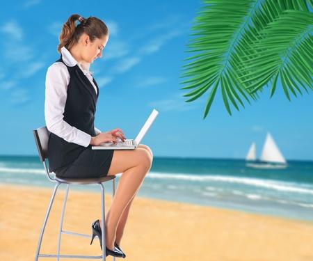 palm computer: Businesswoman on the beach.  Stock Photo