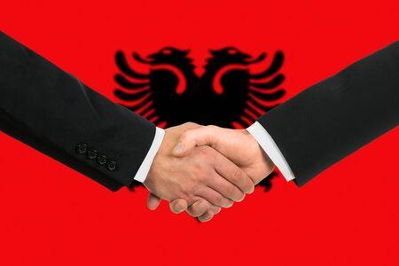 albanian: The Albanian flag and business handshake