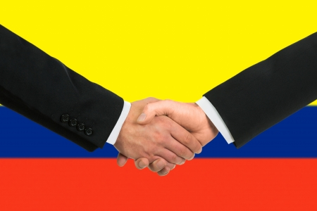 colombian flag: The Colombian flag and business handshake