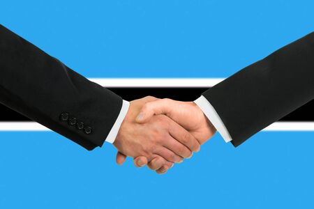 The Botswana flag and business handshake photo
