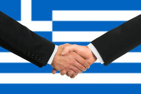 The Greek flag and business handshake photo