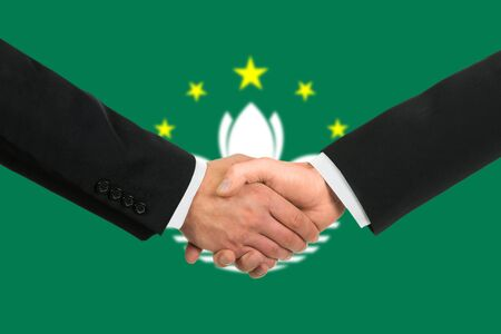 The Macau flag and business handshake photo