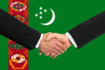 The Turkmen flag and business handshake photo
