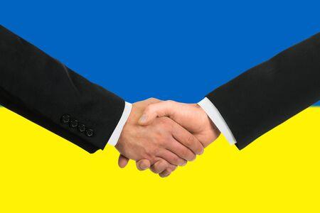 The Ukrainian flag and business handshake photo