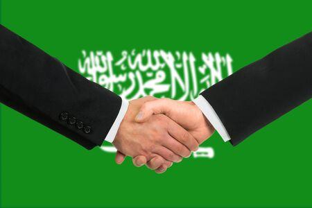 The Saudi Arabia flag and business handshake photo