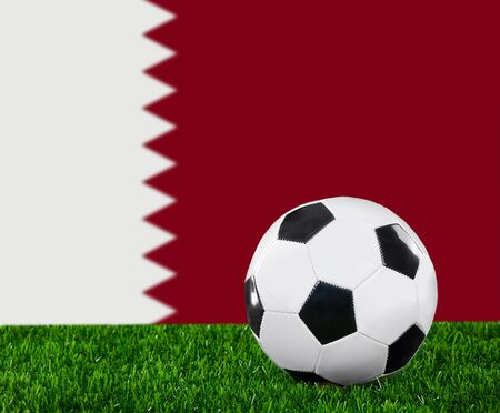 The Qatari flag and soccer ball on the green grass. photo