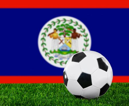 The Belize flag and soccer ball on the green grass. photo