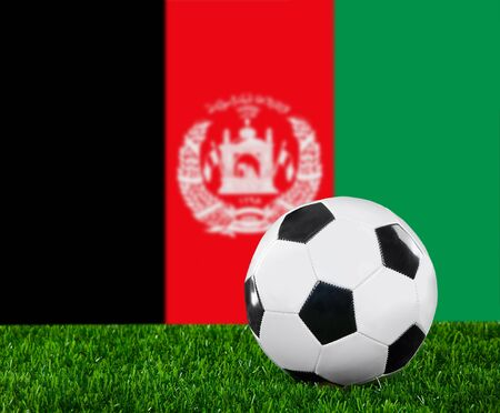 afghan flag: The Afghan flag and soccer ball on the green grass.