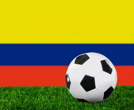 The Colombian flag and soccer ball on the green grass. Stock Photo