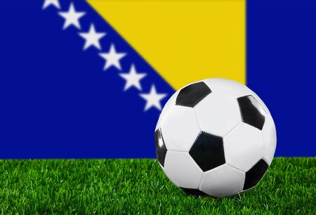 The Bosnia and Herzegovina flag and soccer ball on the green grass. photo