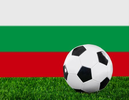 The Bulgarian flag and soccer ball on the green grass. photo